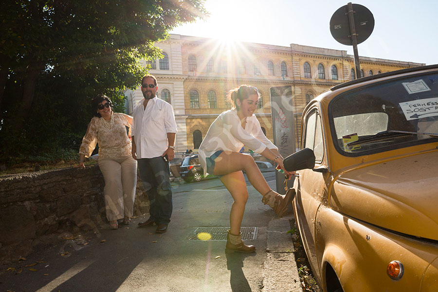 Trying to enter a Fiat 500 in Rome Italy during a photographer session