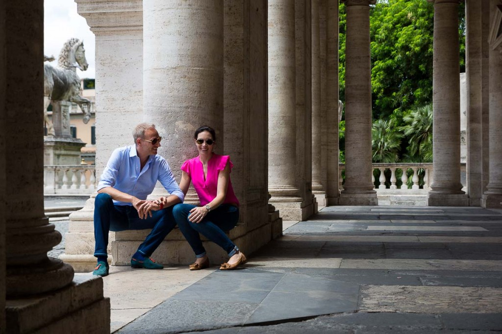 Couple sitting down during under the columns of Piazza Campidoglio
