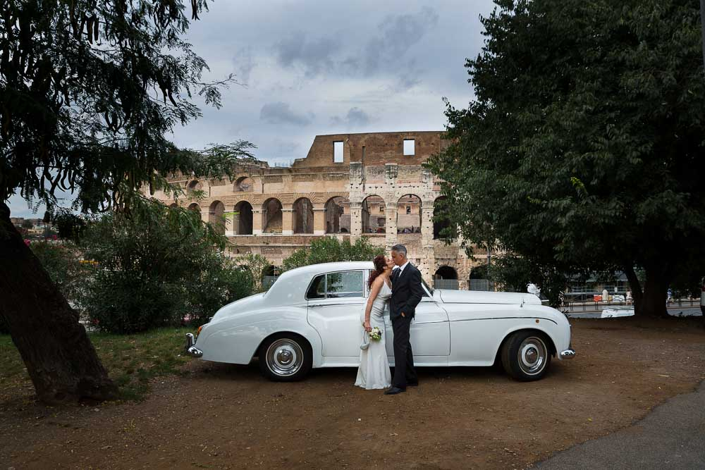 Pictures taken by the vintage Rolls Royce car placed in front of the Coliseum in Rome Italy.