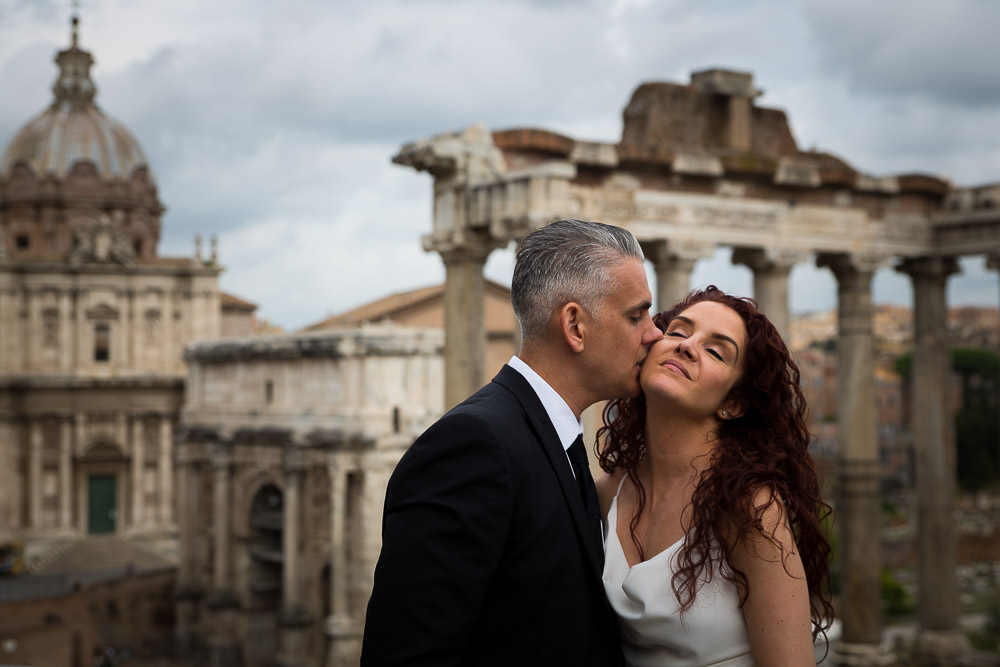 Groom kissing the bride aster the wedding by the Roman Forum.