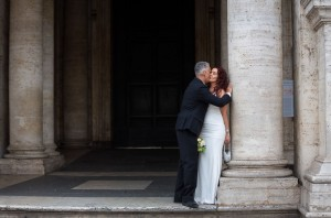 Newlyweds romantically kissing in a square.