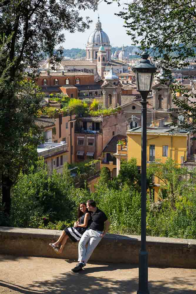 Couple leisurely on vacation enjoying the sun and the view from Parco del Pincio
