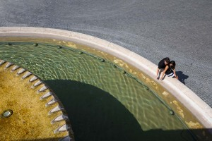 Artistic image of a couple over a water fountain in Piazza del Popolo