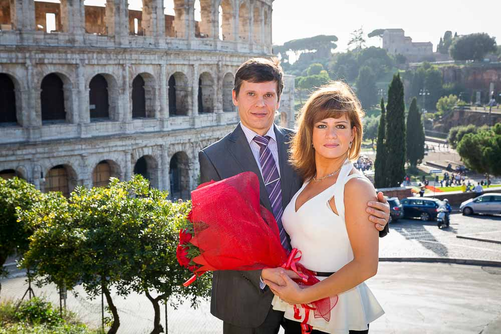 Couple posing in front of the Colosseum in Rome Italy during a photo tour.