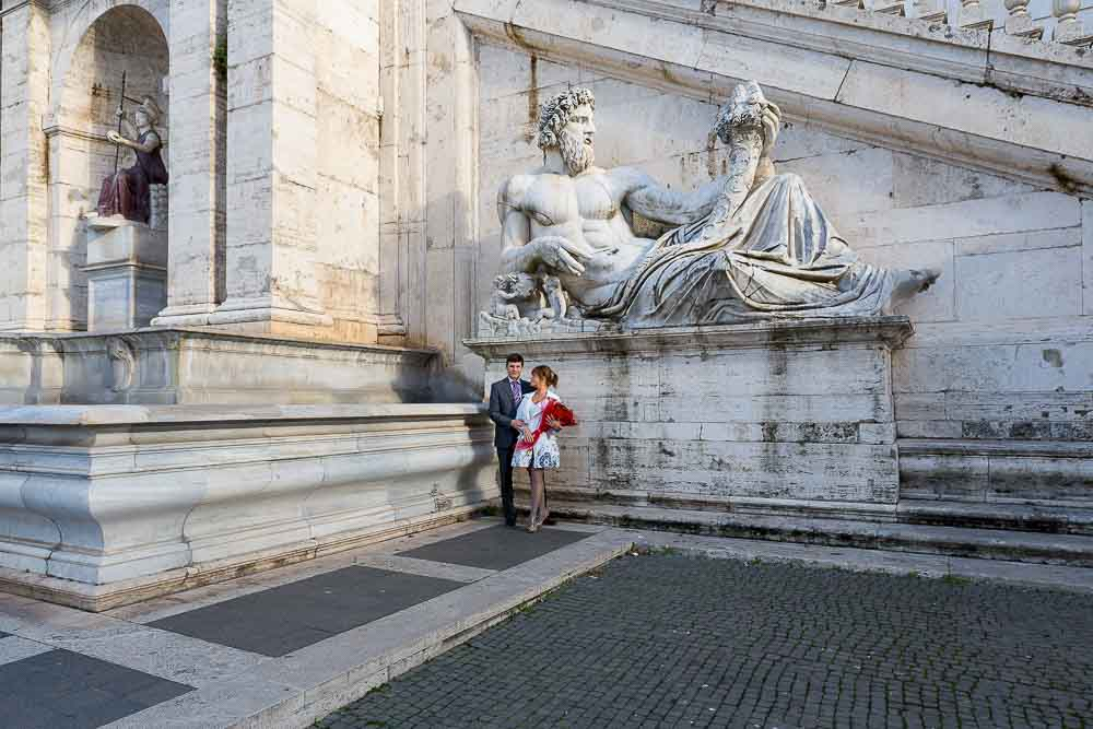 Image of a couple standing before an ancient statue in Piazza del Campidoglio.