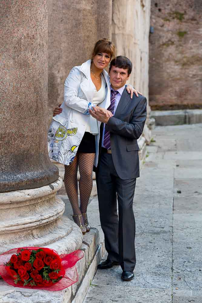 A couple posed next to a column.