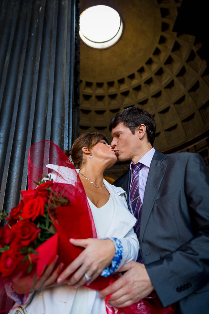Kissing under the light of the Roman Pantheon during an engagement phototour.