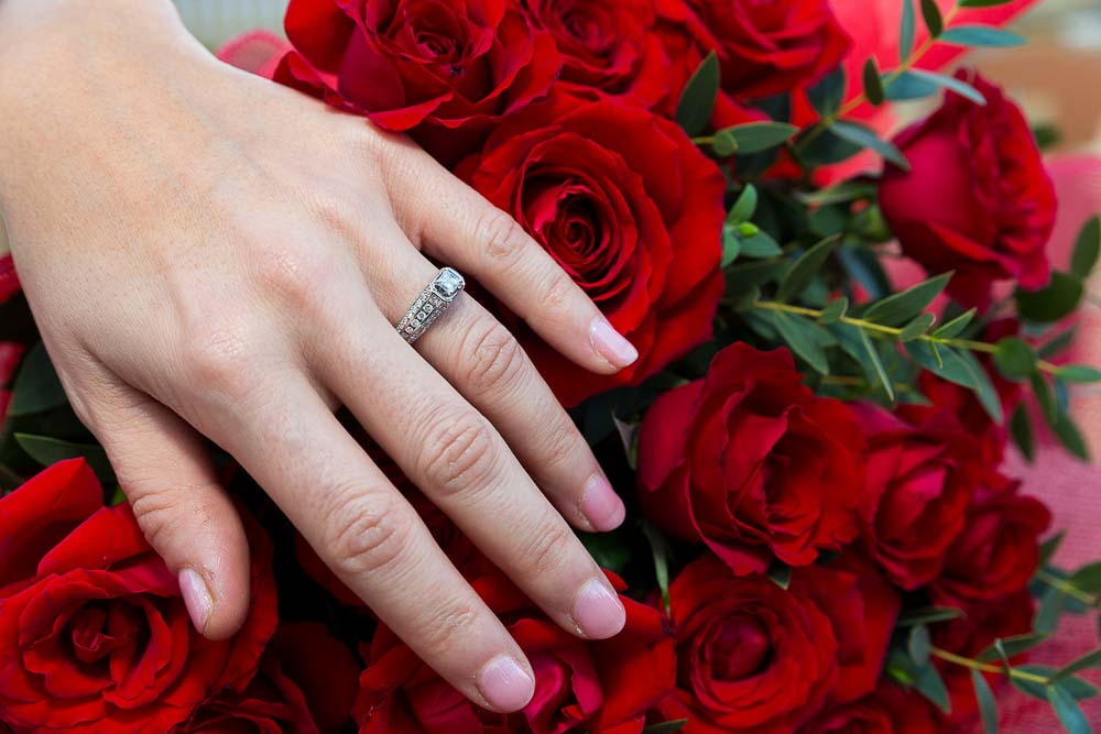 Engagement ring close up over red roses.
