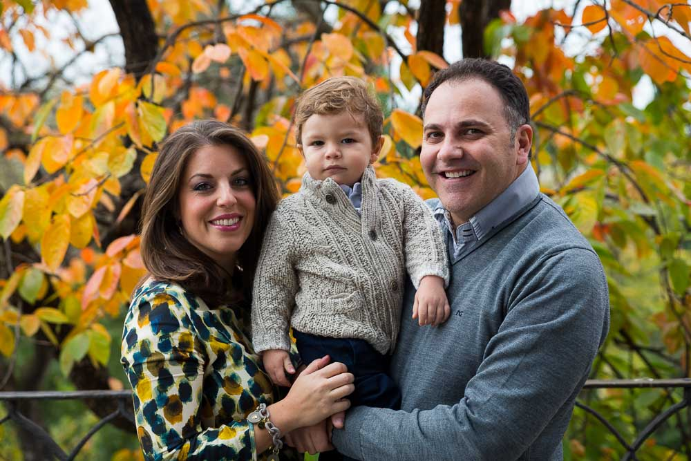 Family portrait photo session in the fall. Autumn tree in the background.