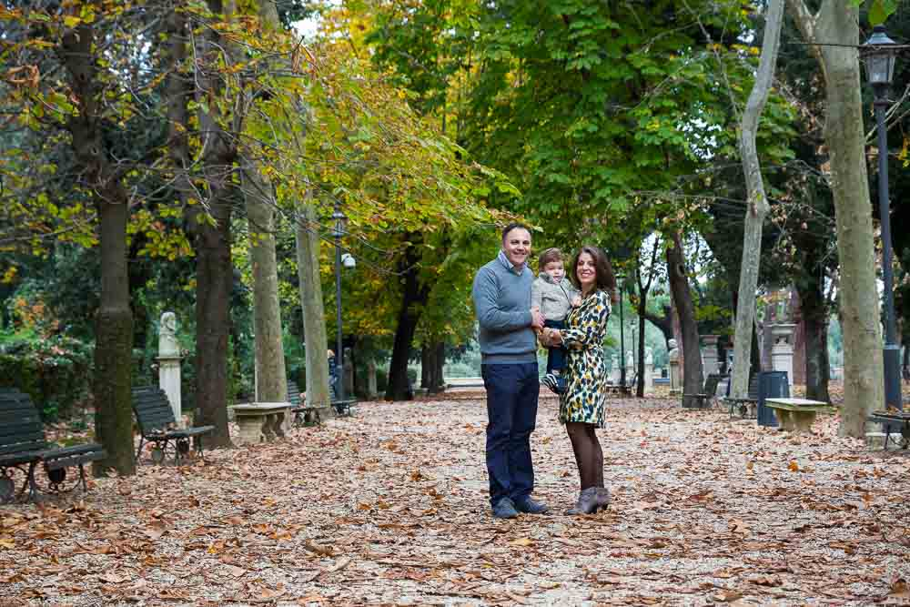 Park setting for a family shoot with trees on the sides and fallen leaves on the ground