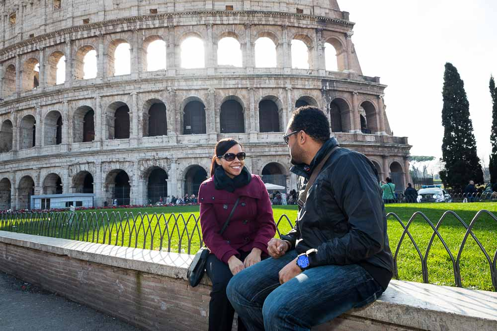 Couple sitting down before the view of the Roman Colosseum