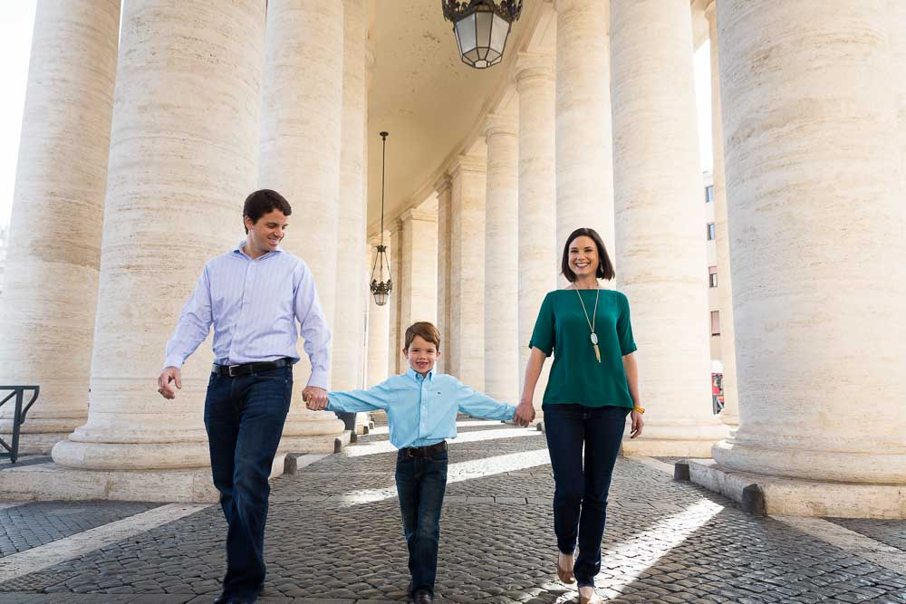 Rome family photo session walking together under the columns of St. Peter
