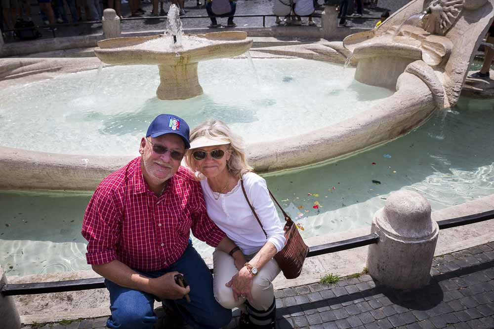 Tourist couple sitting down on the barcaccia water fountain at the Spanish steps
