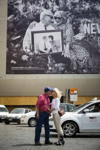 Kissing underneath a publicity billboard poster