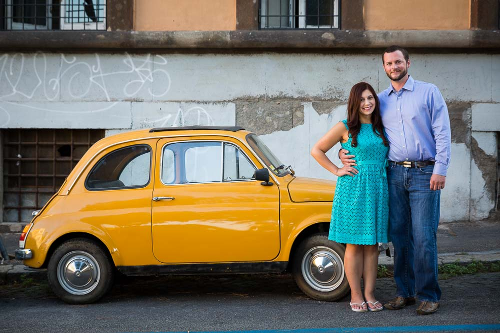 Couple standing in front of an Italian vintage car during a photo shoot
