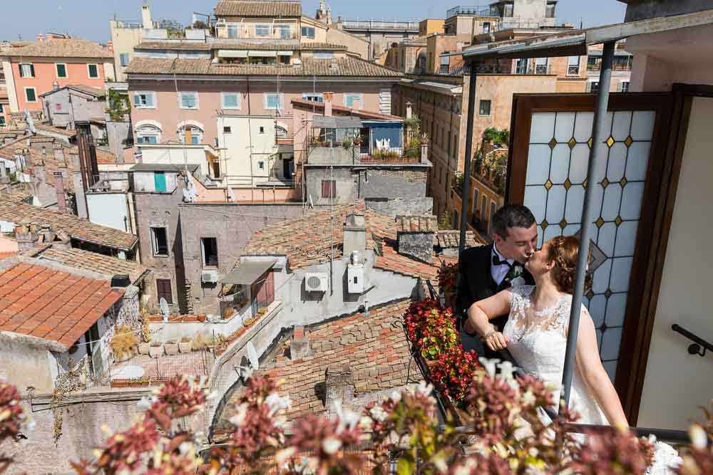 Bride and groom kissing on top of the Rome rooftops