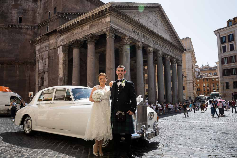 Poising in front of the vintage wedding car before getting married